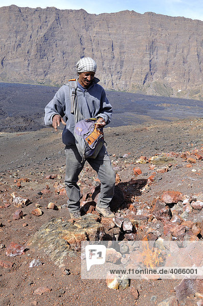 Mountain guide igniting thin branches with the heat of the volcano  Pico de Pequeno  Pico de Fogo Volcano  Fogo Island  Cape Verde Islands  Africa