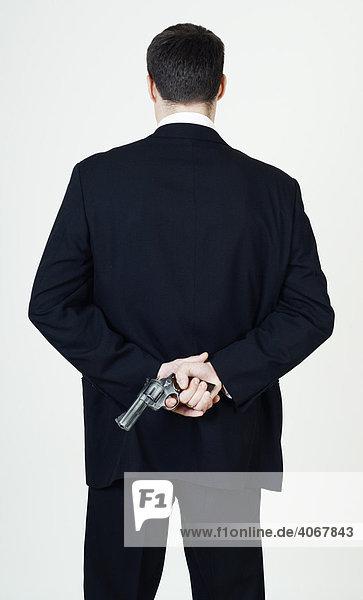 Mann hält Revolver hinter dem Rücken versteckt