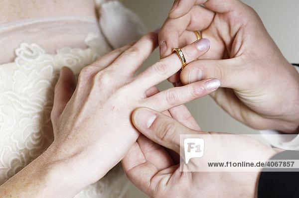Bräutigam steckt seiner Braut den Ehering an