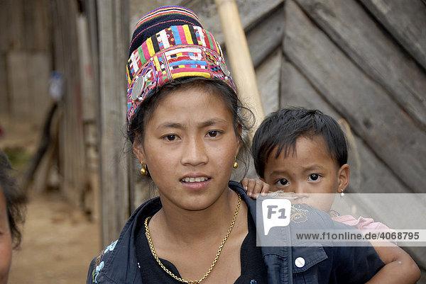 Junge Frau der Akha Loma Ethnie mit Kind auf dem Rücken trägt traditionellen Kopfschmuck  Ban Noy  Phongsali Provinz  Laos  Südostasien