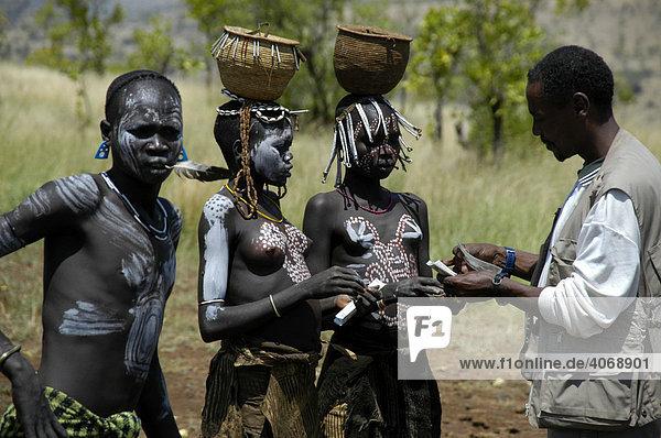 Junge Mädchen mit freiem Busen  Farbe im Gesicht und einem Gefäß auf dem Kopf vom Volk der Mursi verhandeln mit modern gekleidetem Äthiopier  bei Jinka  Äthiopien  Afrika