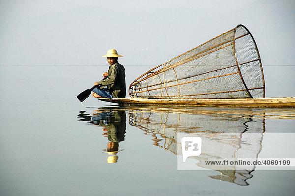 Fischer rudert im Boot mit Fischreuse  Inle See  Shan State  Birma  Burma  Myanmar  Südostasien  Asien