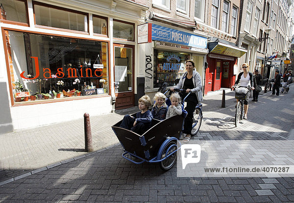 Woman and children on a bicycle equipped with a child carriage  Zeedijk Straat  Centrum  Amsterdam  Netherlands  Europe