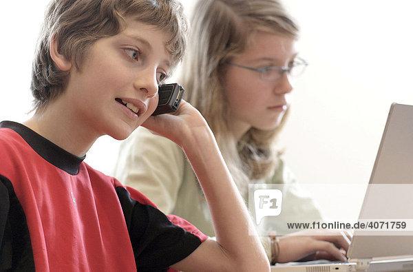 Ein Junge  10 Jahre alt  telefoniert mit einem Handy und seine Schwester  13 Jahre alt  sitzt an einem Laptop
