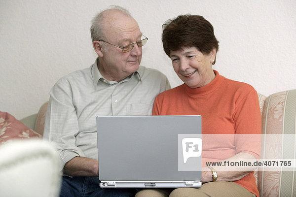 Seniorenpaar sitzt zusammen vor einem Laptop