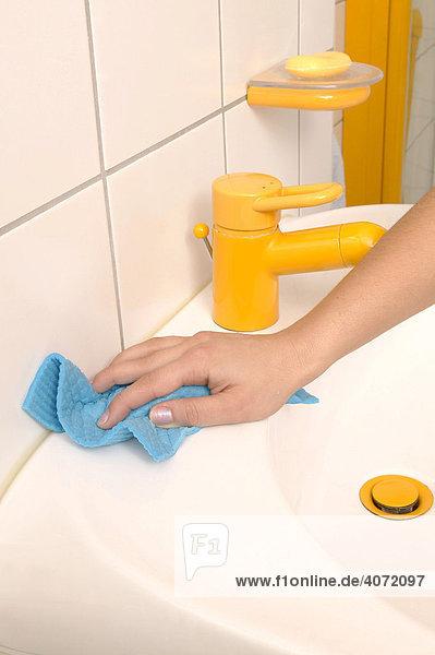 Eine Hand putzt ein Waschbecken