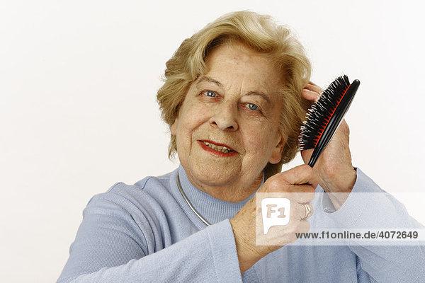 Alte Dame  80-jährige  mit Haarbürste