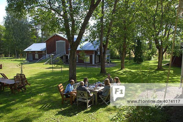 Personen an einem Tisch  draußen  Sommerleben auf dem Land bei Porvoo  Finnland  Europa
