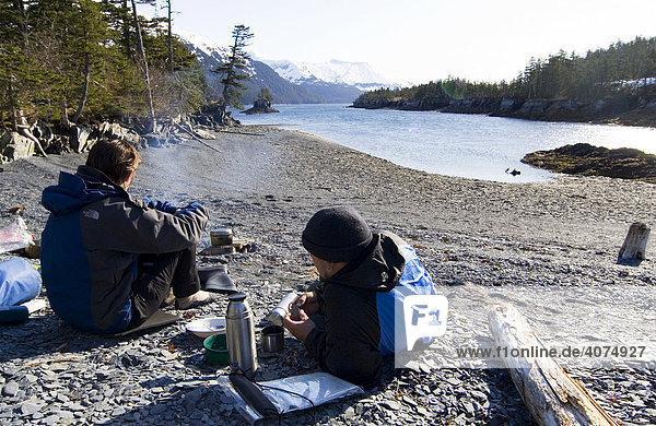 Young couple resting at campfire  beach  evening  Surprise Cove  Pacific Coast  Prince William Sound  Alaska  USA