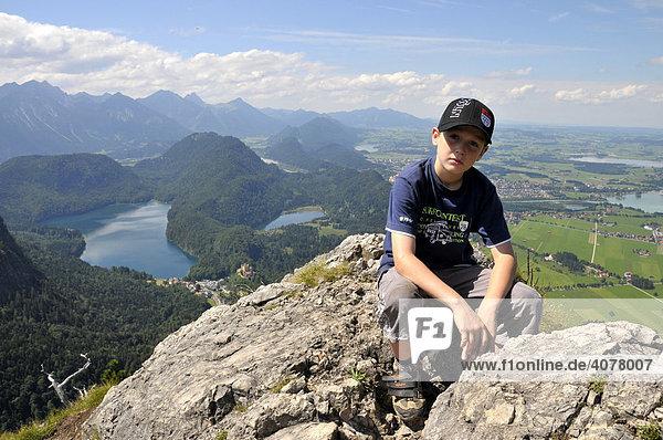 Ein achtjähriger Junge macht Rast  Tegelberg  hinten der Alpsee und Füssen  Allgäuer Alpen  Bayern  Deutschland  Europa