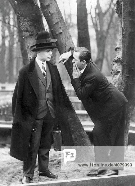 Mann trägt zwei Hüte übereinander  historische Aufnahme  ca. 1940