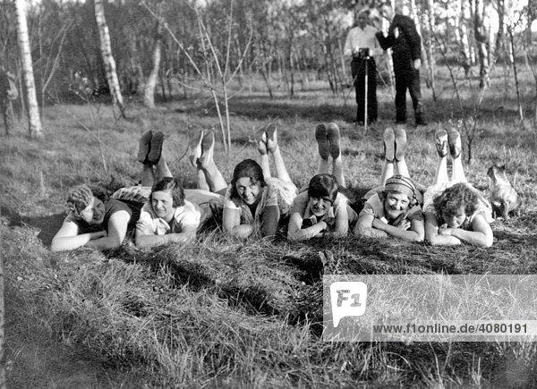 Historische Aufnahme  Frauen liegen mit angewinkelten Beinen im Gras