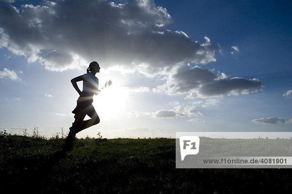 Frau beim Lauftraining als Silhouette vor Himmel mit Wolken bei Gegenlicht