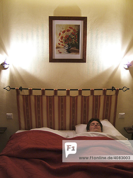 Sleeping woman lying in a hotel bed.