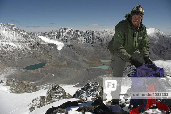 Bergsteiger mit Rucksack auf einem Gipfel mit Ausblick in die Bergwelt des Turgen Uul Kharkhiraa Mongolischer Altai bei Ulaangom Uvs Aimag Mongolei
