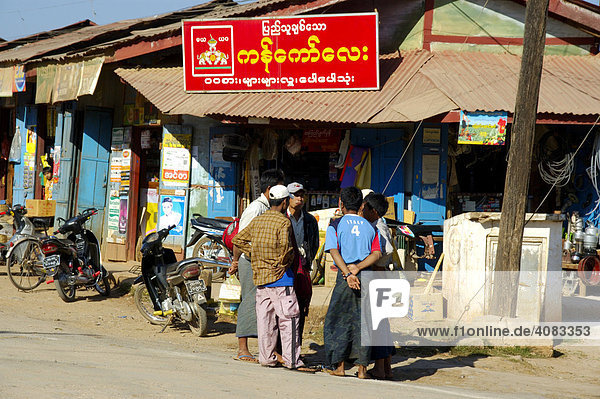 Group of men standing at a shop with sign in Burmese script Pindaya Shan State Burma