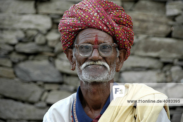 Portrait Rajpute man wearing red turban glasses and a moustache in front of ay stone wall Kelwara Rajasthan India
