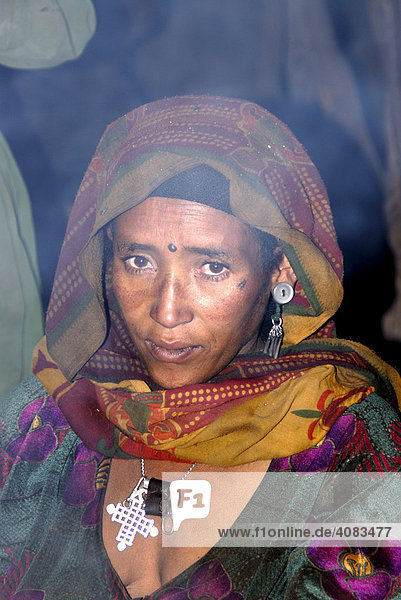 Portrait woman wearing kerchief and cross in the fume Geech Semien Mountains Ethiopia