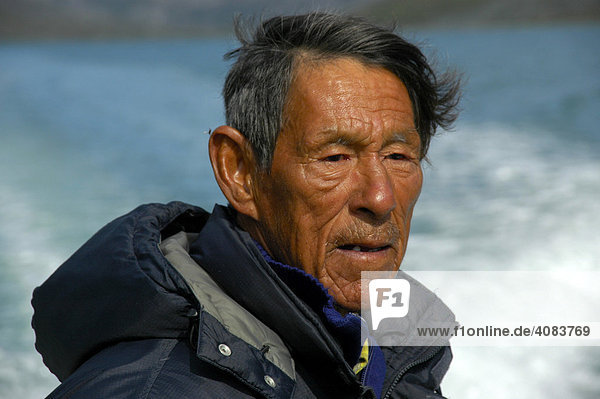 Portrait Inuit Greenlander wearing a down jacket with hood in Qinngertivaq Fjord Eastgreenland
