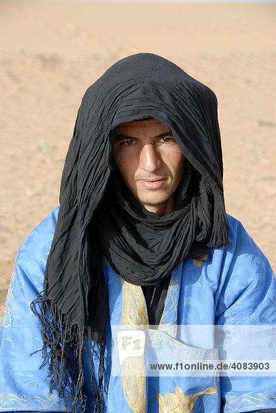 Portrait Tuareg dressed in blue robe and black turban Erg Chebbi Merzouga Morocco