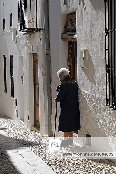 Old woman with cane  narrow alleyway in the historic centre of Benissa  Alicante  Costa Blanca  Spain