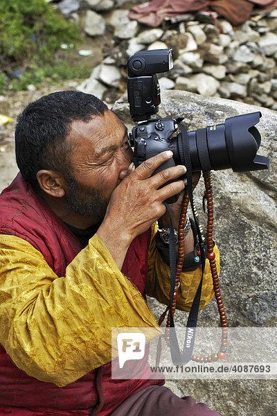Mönch mit Kamera  Chim-puk Hermitage bei Tsethang nahe Lhasa  Tibet  Asien