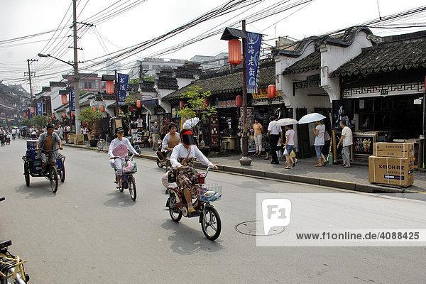 Straße im alten Shanghai  Kabelchaos  kleine Läden  Mopedfahrer  Fahrradrikscha  Shanghai  China  Asien
