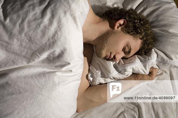 Junger Mann im Bett  schlafend