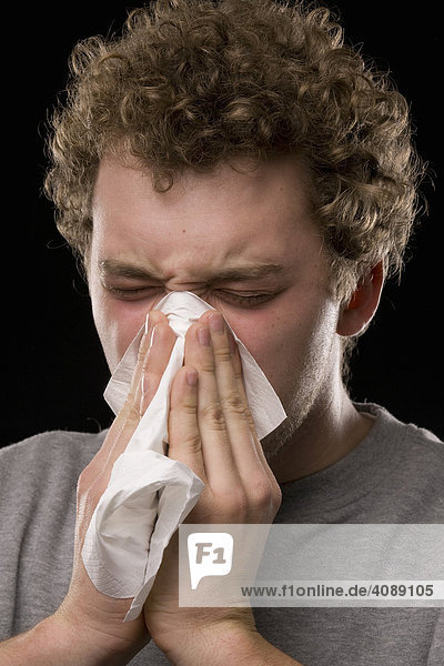 Junger Mann  Nase putzend