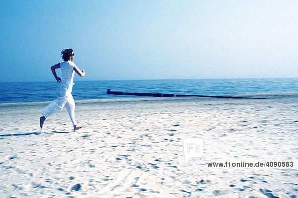 Junge Frau in weiss joggt am Strand entlang