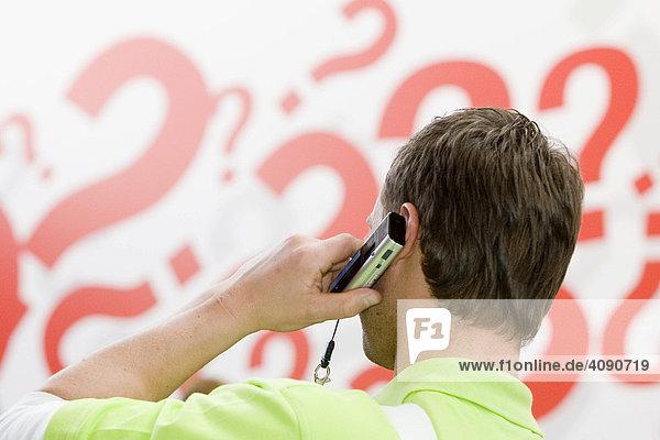 Ein Mann telefoniert mit einem Handy vor einer Wand mit Fragezeichen