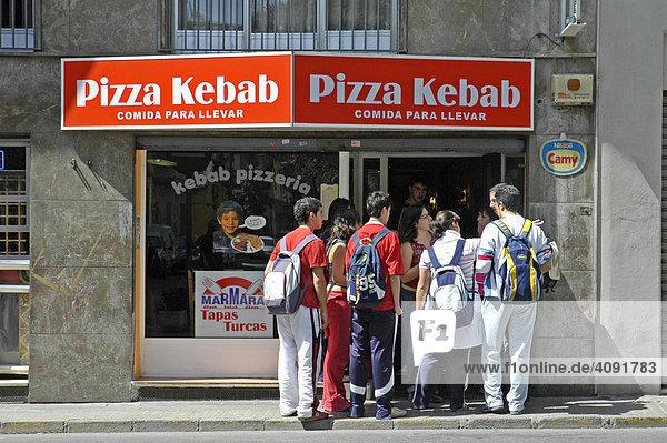 Schulkinder mit Rucksaecken draengeln sich in die Tuer einer Pizza und Kebab Bude  Elx  Elche  Costa Blanca  Spanien
