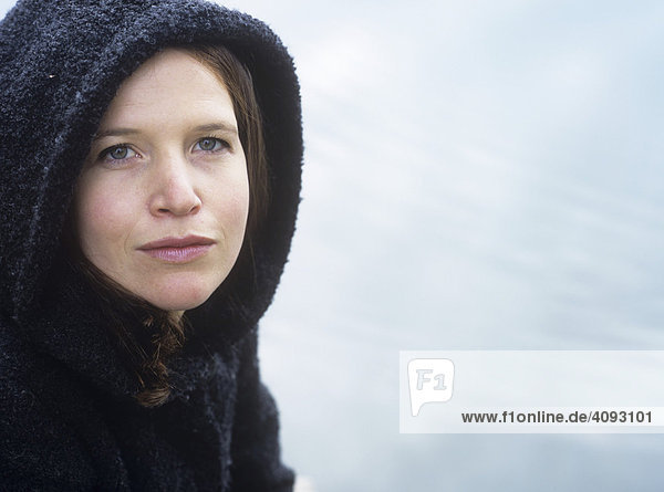 Hooded woman by the water