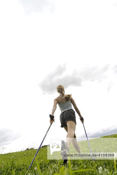 Young woman Nordic walking (ski walking)