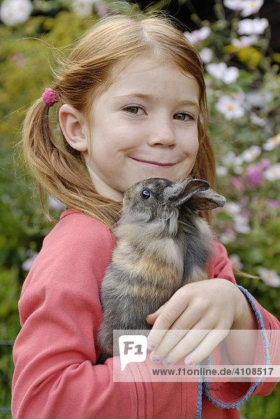 Kleines Mädchen mit Zwerghase (Oryctolagus cuniculus)