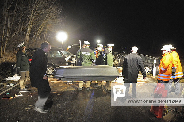 Victim of a heavy traffic accident is carried away from the accident scene by the undertakers in a casket  Gomadingen  Reutlingen Region  Baden-Wuerttemberg  Germany  Europe