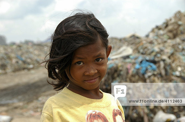 Sad girl rummaging through rubbish at the Stung Meanchey Municipal Garbage Dump in the south of Cambodia's capital Phnom Penh where she lives with many other very poor people who try to survive on less than a dollar a day  Phnom Penh  Cambodia  Southeast Asia