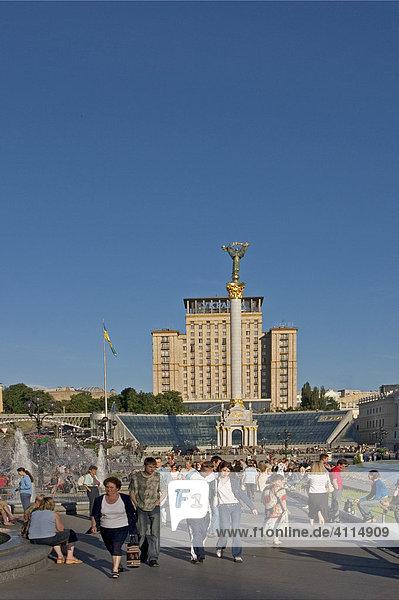 Ukraine Kiev Unabhängigkeits Platz mit Unabhängigkeitssäule Gebäude der Nationalen Musikakademie Cajkovskij Konservatorium rechts Hotel Kiev mitte Glasfront des Einkaufscentrums Globus II Menschen auf dem Platz vor der Unabhängikeitssäule sitzen einkaufen unterhalten blauer Himmel 2004
