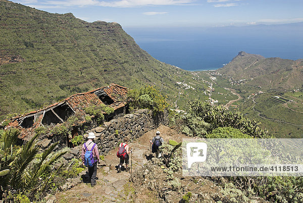 Hiker passing a tumbledown house in the valley of Hermigua  La Gomera Island  Canary Islands  Spain  Europe