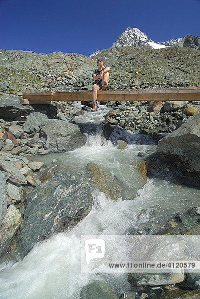 Hiker sitting on a wooden bridge over a mountain brook  National Park Hohe Tauern  Tyrol  Austria