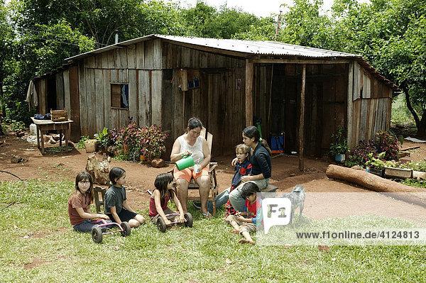 Eine Gruppe Frauen und Kinder machen Pause vor dem Haus  Paraguay  Südamerika