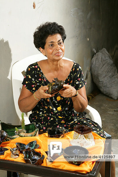 Woman displaying her wares at Ana Correia handicrafts bazaar in Georgetown  Guyana  South America