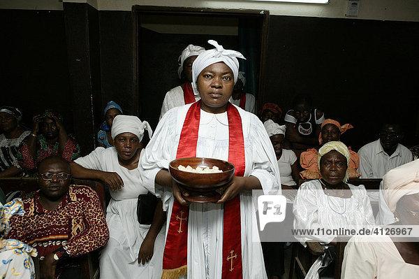 Frau verteilt Abendmahl  Brot  Gottesdienst  Douala  Kamerun  Afrika