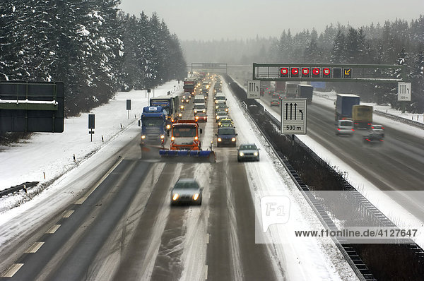Highway at wintry road conditions  traffic jam on the higway  snowplough cleaning the highway