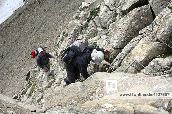 Two mountain climbers on a fixed rope route on the way down  Parseier Spitz  Lechtaler Alps  Tyrol  Austria