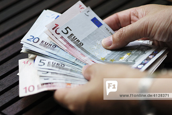 Frau zählt Geld  Euro Banknoten