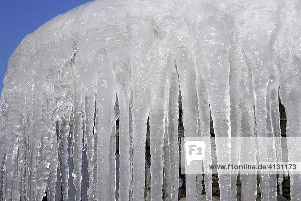 Eiszapfen am Rand eines Brunnens hängend