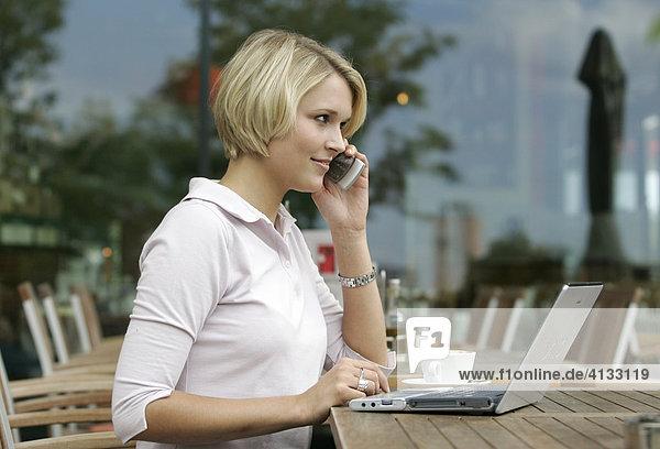 Geschaeftsfrau mit Laptop und Mobiltelefon