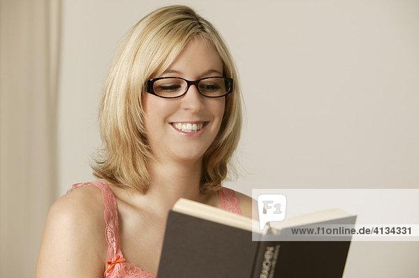 Junge blonde Frau mit Brille liest ein Buch