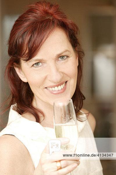 Rothaarige Frau im mittleren Alter mit Sektglas  lächelt